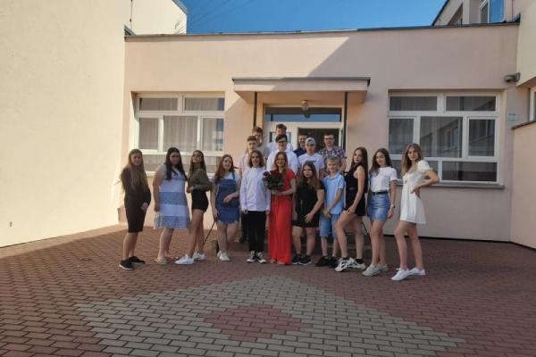Grupa ósmo klasistów przed budynkiem szkoły